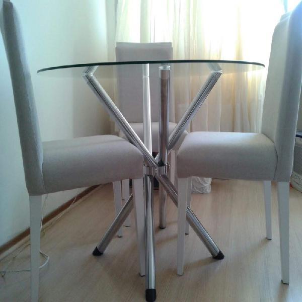 Mesa redonda de vidro com três cadeiras de madeira