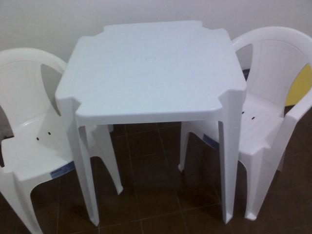 Uma mesa e duas cadeiras de plastico