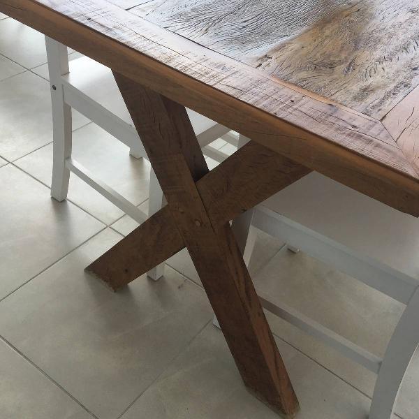 Mesa em madeira de demolição com quatro cadeiras brancas