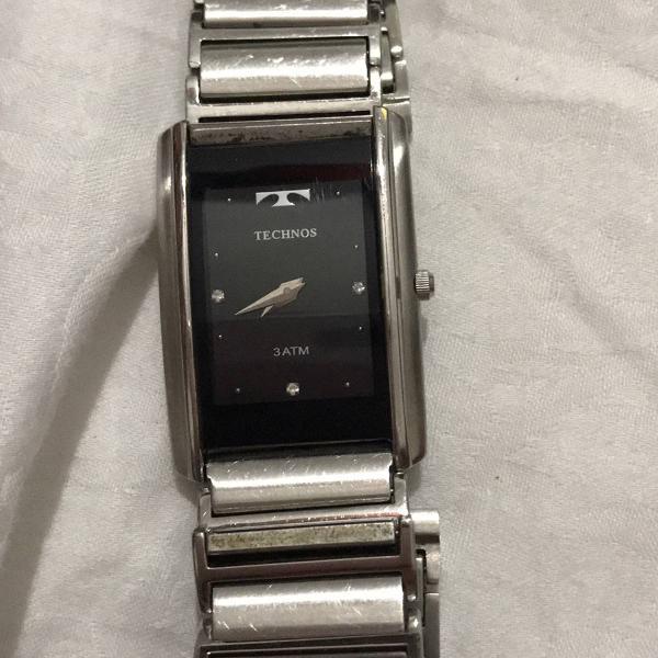 Relógio de pulso prateado com caixa retangular e fundo