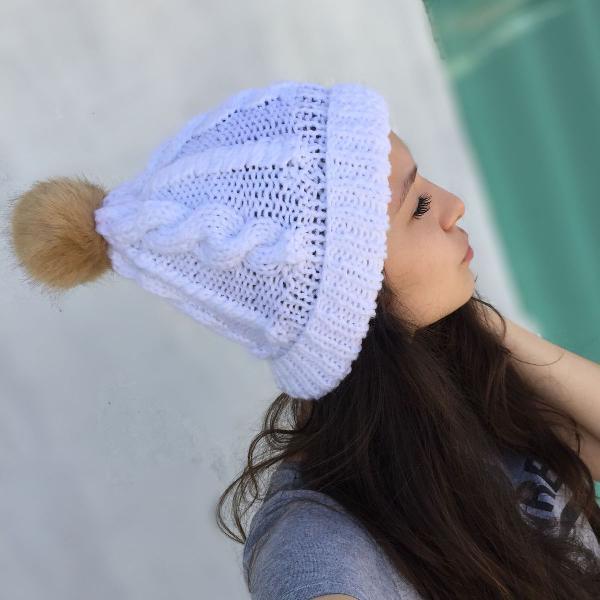 Touca branca com pompom feito de tricô à mão