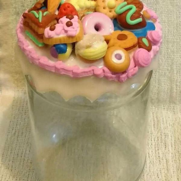 Caixas e potes com tampas decoradas com doces.