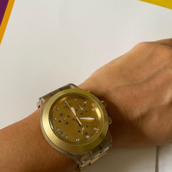 Relógio swatch dourado com transparência