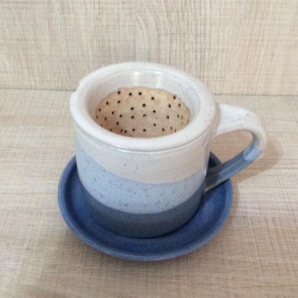 Xícara com pires e coador de chá ou café